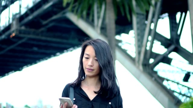 young woman with smart phone  walking on the street - capelli neri video stock e b–roll