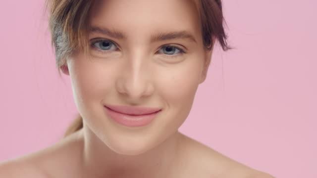 pürüzsüz sağlıklı cilt ile genç kadın kamera ve gülümseme bakıyor. - sadece genç bir kadın stok videoları ve detay görüntü çekimi