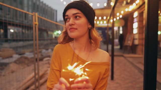 Young woman with sparklers celebrating new year in city video