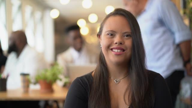 vídeos y material grabado en eventos de stock de mujer joven con necesidades especiales en el retrato de la oficina-ambiente del negocio - adulto