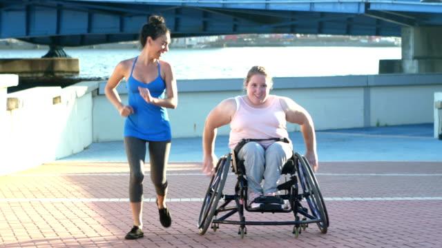vídeos y material grabado en eventos de stock de mujer joven con espina bífida, amiga, corriendo cuesta arriba - deportes en silla de ruedas