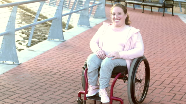 Young woman with spina bifida, sitting in wheelchair A young woman with spina bifida, sitting in a wheelchair, in the city on the waterfront. orthopedic equipment stock videos & royalty-free footage