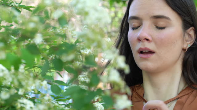 Young woman with spring allergies A woman outdoors standing near a plant suffers allergies. pollen stock videos & royalty-free footage