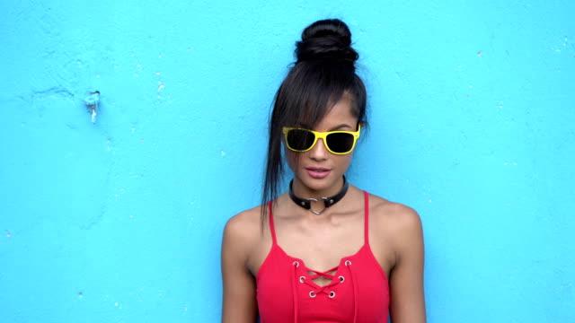 vídeos y material grabado en eventos de stock de mujer joven de 4k con la situación de las gafas de sol en frente de pared azul - color vibrante