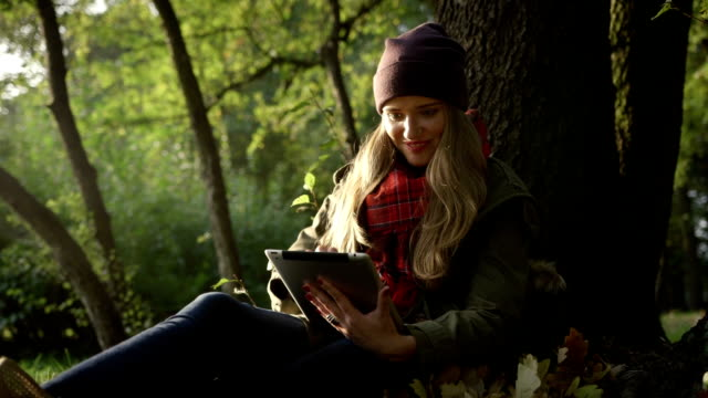 Young woman with tablet computer in beautiful autumn park. video