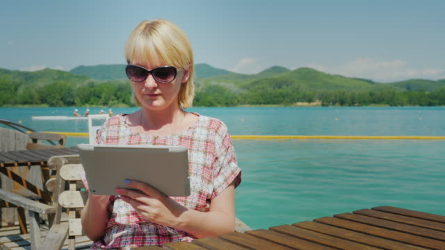 Young woman with the tablet. Sitting in a cafe on the terrace on the background of the picturesque lake and the green mountains. Spain video
