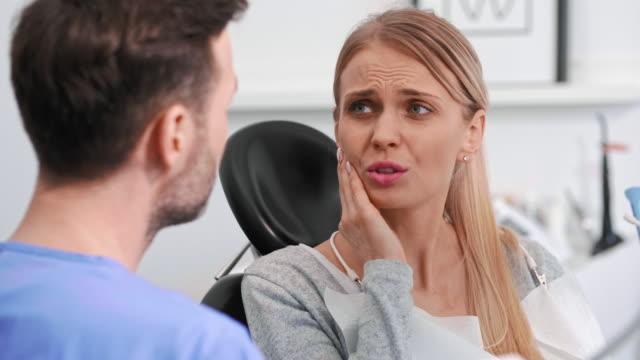 diş ağrısı olan genç kadın dişçi kliniğinde diş hekimi ile konuşuyor - diş sağlığı stok videoları ve detay görüntü çekimi