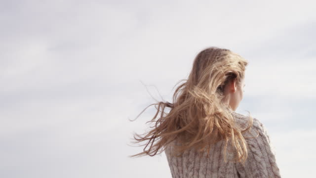 young woman with tousled hair standing at terrace - spettinato video stock e b–roll