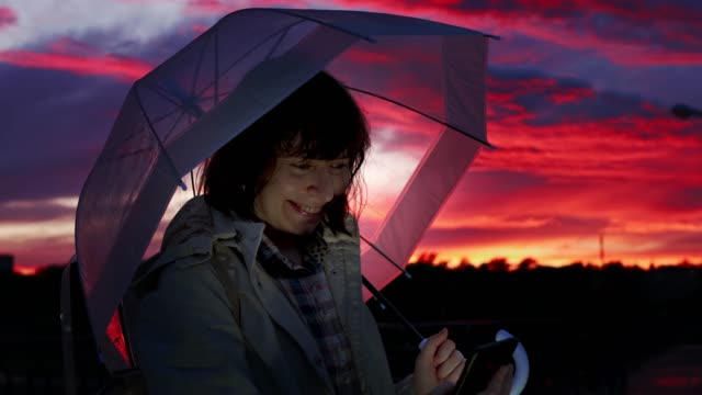 Young woman with transparent umbrella is typing texting on smartphone at dusk. video