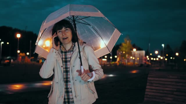 Young woman with transparent umbrella speaks on smartphone and walks in rain. video