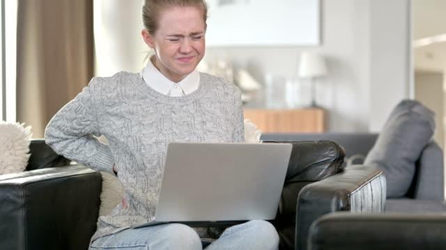 vídeos de stock, filmes e b-roll de jovem mulher trabalhando e tendo dor nas costas em casa - ortopedia