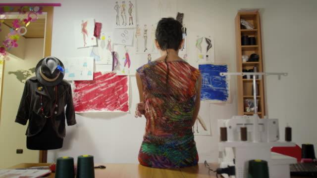 Jeune femme travaillant comme styliste envisagent dessins en studio - Vidéo