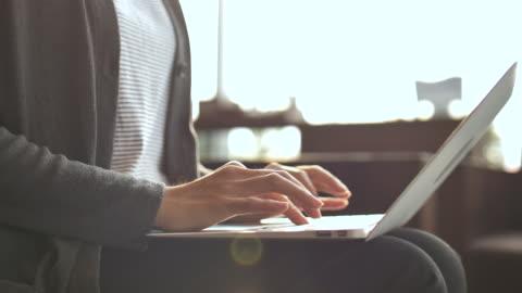vídeos y material grabado en eventos de stock de una mujer joven trabajando en la laptop y escribir en el teclado del ordenador portátil - mecanografiar