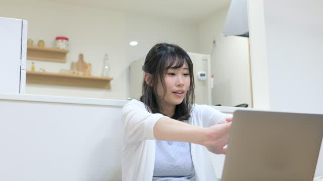 自宅で働く若い女性、ダイニングルームでストレッチ - パソコン 日本人点の映像素材/bロール