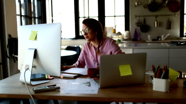 vidéos et rushes de jeune femme travaillant de la maison - vidéoconférence