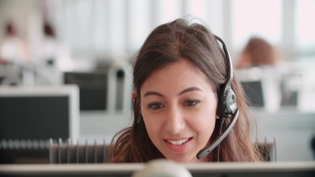 Young woman working in a call centre using a headset Young woman working in a call centre using a headset call centre videos stock videos & royalty-free footage