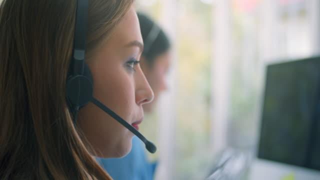 ung kvinna som arbetar i ett callcenter, närbild - telecom bildbanksvideor och videomaterial från bakom kulisserna