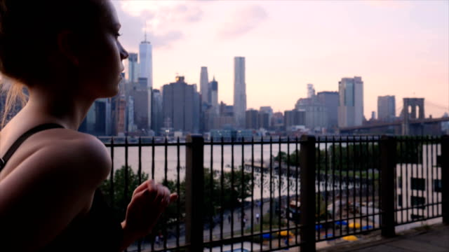 Young woman working out against the New York City waterfront sunset video