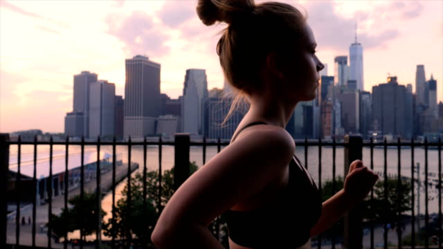 Young woman working out against the New York City waterfront sunset Young woman working out against the New York City waterfront sunset recreational pursuit stock videos & royalty-free footage