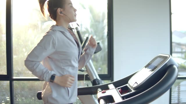 young woman working out and jogging on treadmill at gym - sprzęt do ćwiczeń filmów i materiałów b-roll