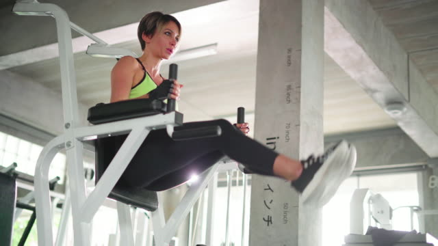 young woman working out on exercise machine - reggiseno sportivo video stock e b–roll