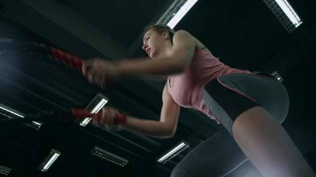 Young woman working out with battle ropes video