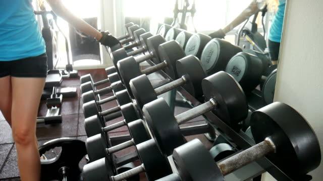 ung kvinna som arbetar med vikter i gymmet - black woman towel workout bildbanksvideor och videomaterial från bakom kulisserna
