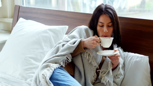 Young woman wrapped in blanket having tea 4k video