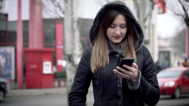 Ung kvinna skriver SMS på mobil telefon i staden video