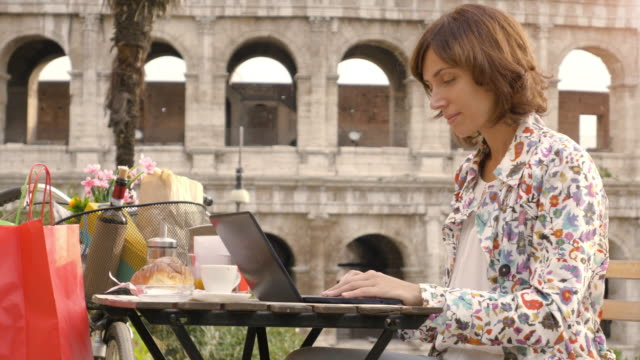 young woman writing and working on her laptop computer sitting at the table outside in a bar in front of the colosseum in rome. elegant beautiful dress and colorful shopping bags. - итальянская культура стоковые видео и кадры b-roll