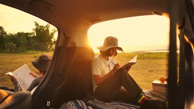 日没時に車の中で本を書く若い女性 - 楽しい点の映像素材/bロール