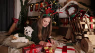 istock Young woman writing Christmas card on Christmas at home 1288601634