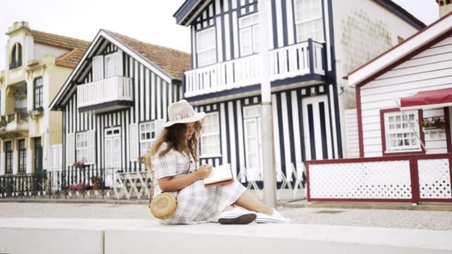 vídeos de stock e filmes b-roll de young woman writing in notebook on street - aveiro