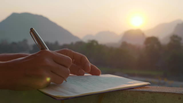 Young woman writing morning pages in diary outdoor, close-up in slow motion