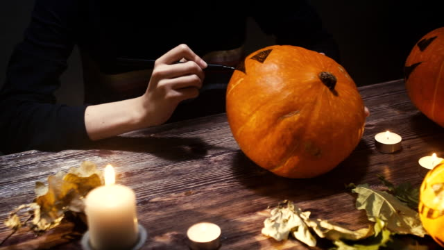 young womanDrawing eyes and mouth on Halloween pumpkin to carve a Jack 'o' Lantern. The winter squash embodies the spirit of autumn like: Halloween,Thanksgiving, harvest parties & Pumpkin Spice lattes video