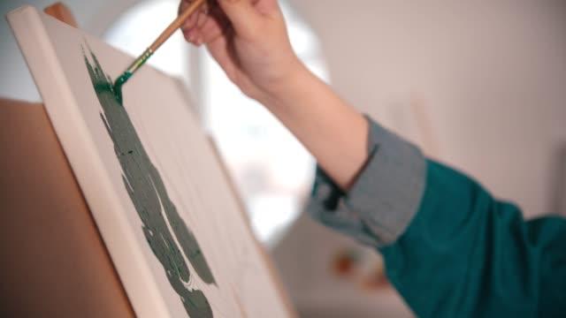 vidéos et rushes de peinture de main d'une jeune femme avec une couleur verte sur la toile dans l'atelier d'art - toile à peindre
