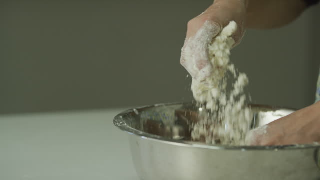 A Young Woman's Hands Break Up Chunks of Butter into Flour (Cutting In and Mixing) to Make a Dough in a Metal Mixing Bowl A Young Woman's Hands Break Up Chunks of Butter into Flour (Cutting In and Mixing) to Make a Dough in a Metal Mixing Bowl mixing bowl stock videos & royalty-free footage