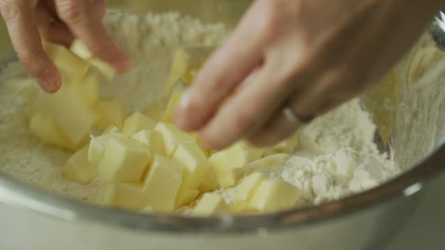 a young woman's hands cut butter into small pieces with a large kitchen knife on a wooden cutting board and then pick up the butter and sprinkle it over flour in a metal mixing bowl - impasto video stock e b–roll