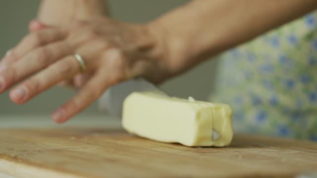 vídeos de stock, filmes e b-roll de lugar de mãos de uma mulher jovem manteiga para um corte de madeira da placa e usa uma faca de cozinha grande corte na cozinha de um interior acolhedor - gordura