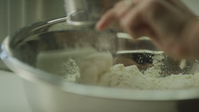 a young woman's hands pour flour from a metal measuring cup into a mixing bowl - impasto video stock e b–roll
