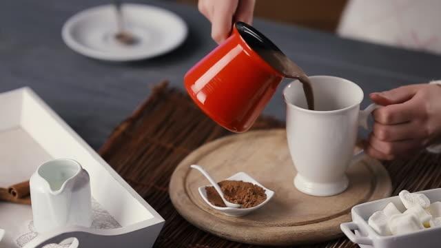 vídeos de stock, filmes e b-roll de mãos da mulher nova que derramam o chocolate quente no copo. - chocolate quente