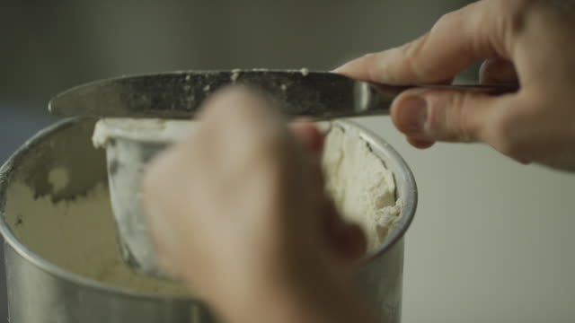 A Young Woman's Hands Use a Metal Measuring Cup to Scoop Flour from a Canister and then Use a Kitchen Knife to Remove Excess from the Top Before Pouring It Into a Mixing Bowl