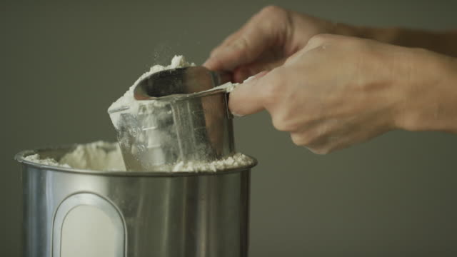 A Young Woman's Hands Use a Metal Measuring Cup to Scoop Flour from a Canister and then Use a Kitchen Knife to Remove Excess from the Top