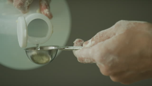 A Young Woman's Hands Use a Small Metal Measuring Spoon to Measure White Vinegar While Baking/Cooking