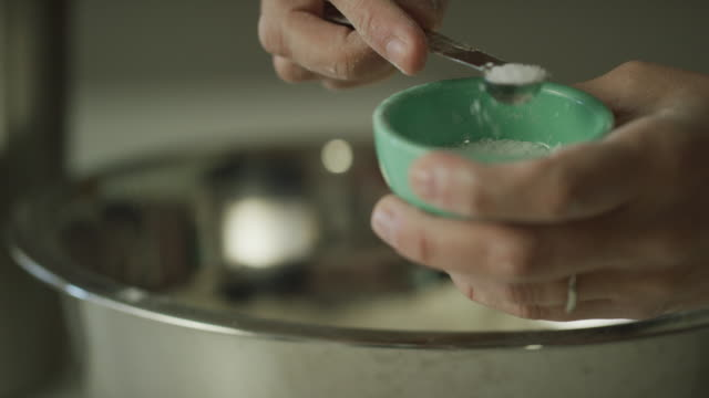 a young woman's hands use a small metal measuring spoon to scoop salt from a small bowl next to a mixing bowl - salt video stock e b–roll