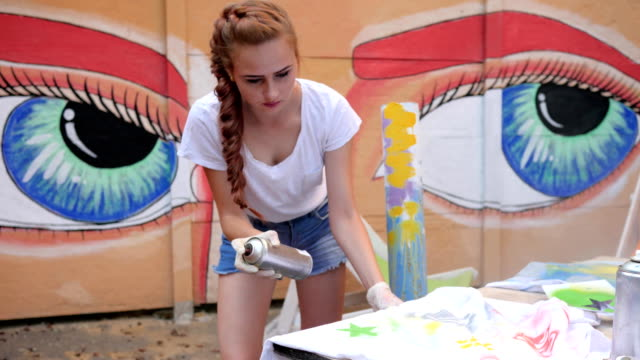 young womans Painted clothes with spray paint on background of graffiti, design clothes of handmade outdoors