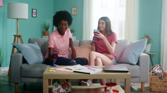 Young Women Are Chatting and Drinking Beverage Young women, soulmates, Caucasian white and Afro-American, spend time in cozy living room, chatting and gossiping, drink beverage, enjoying their weekend, Slow motion. international match stock videos & royalty-free footage