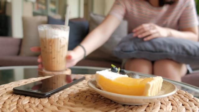Young women are eating desserts and drinking iced coffee.
