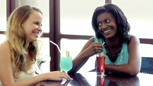 Young women at bar with drinks and couple during date video