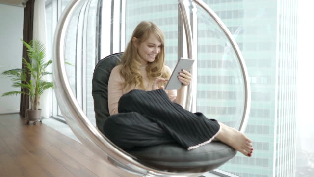 Young women at home sitting on modern chair in front of window and using tablet computer young girl with ipad in living room lounge chair stock videos & royalty-free footage